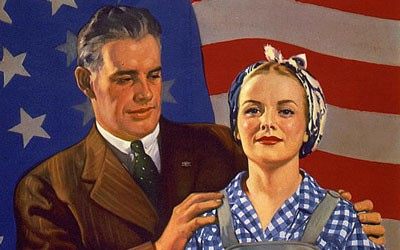 Husband, in suit, and wife in working clothes, standing in front of U.S. flag.