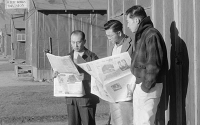 Black and white image three men, two reading newspapers, standing in front of Office of Reports, Free Press.