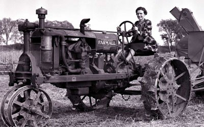 Black and white photo of a female farmer on a tractor.