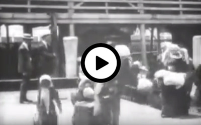 """""""Emigrants Landing at Ellis Island,"""" a contemporary Edison film, shows a large open barge loaded with people of many nationalities, who just arrived from Europe."""