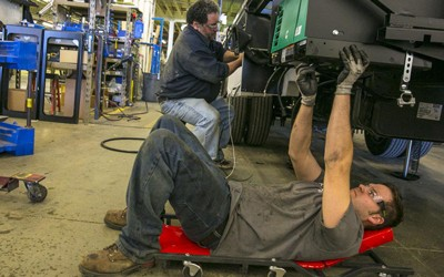 Assembly line workers Jared Maas, right, and Stan Trca work under the chassis of an RV on the Winnebago Industries assembly line in Forest City in March 2016.