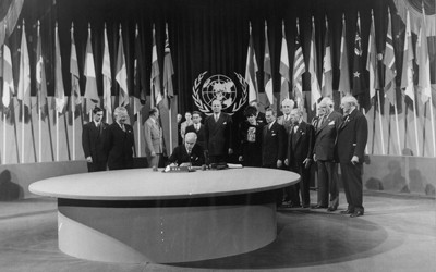 At the conference in San Francisco, Secretary of State Edward Stettinius signs the United Nations charter while President Harry S. Truman (second from left) looks on.  The United States delegation is gathered about.