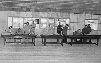 Three tables are seen in a plain looking room with military personnel seen through the background windows.  General Harrison is seated at the table on the left, General Nam is seated at the table on the right.  Both Generals are attended by other staff as they sign the armistice that ended the three year Korean conflict.
