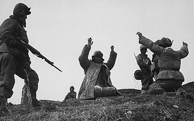 In a grassy hill area, two men are seen kneeling with their arms in the air. Three soldiers are seen on each side of them with guns.  All men are dressed in cold weather gear.