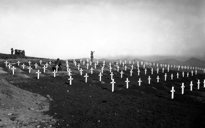 A lone bugler is seen in the background of a Marine cemetery at Hamhung, Korea in 1950.  Dozens of graves are marked with white crosses, each mounded with dirt.  Bare soil is seen throughout the cemetery - no grass has grown.  In the distance is a vehicle and three soldiers standing at attention.  One additional man is seen kneeling amid the graves.