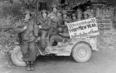 "Seven uniformed, smiling, relaxed soldiers from Iowa are seen seated on an army jeep. They hold a sign that reads: ""Rock of the Marne • Happy New Year • To The Folks at Home."" The background is a wooded hillside with a large amount of sandbags stacked up."