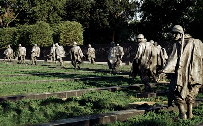 Multiple statues visible in an are of low-lying bushes and granite blocks.  United States flag is seen on the left.  Mature trees are seen in the background.