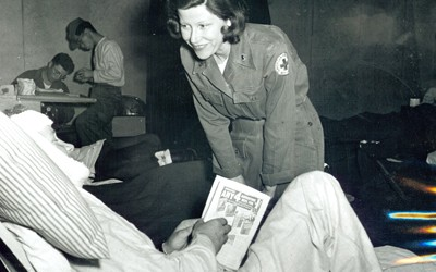 Woman identified as Red Cross worker Mary Jane White of Burlington, Iowa is seen talking with a wounded soldier at a M.A.S.H. hospital.  Ms. White wears a uniform with a Red Cross logo on the left sleeve.  She is bent down in conversation with a wounded soldier who is reclining on a hospital cot.  The patient's head is bandaged, and he holds a magazine in his hands.