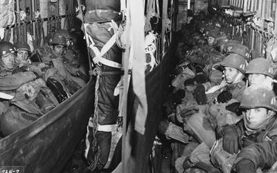 Photo of inside of a cargo plane soldiers lining the two sides of the cargo hold.  Parachute equipment seen in the center hanging from ceiling of the cargo hold.