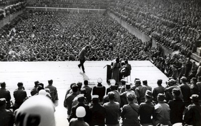 Stage scene with male performer along with a piano, pianist, and female performer.  Stage is surrounded by thousands of seated soldiers, including soldiers seated behind the performers.