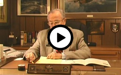Mr. Sinclair is seated at a desk, presumably in an office, dressed in a beige suit and red striped tie. The interviewer is off-camera and asks questions intermittently.