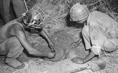 Two men seen squatting down, leaning over circular object they are in the process of burying in the ground.  Each man wears a helmet but no other uniform or safety equipment.  A third man is seen standing behind the man on the left along with a pile of straw in the background.