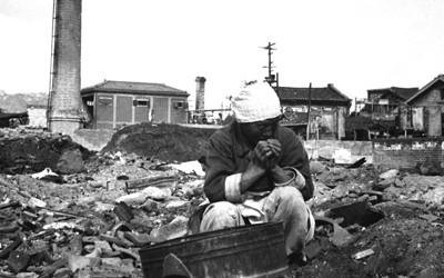 Elderly Korean woman wearing plain-styled shirt, skirt, and head-covering, sits in rubble of some sort of structure.