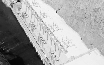 The image shows an aerial view of Hoover Dam with a power station at the top.  On one side there is visible water, and on the other there is none.