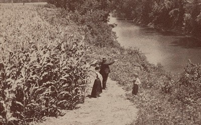 The side-by-side images show a man, woman, and young boy standing at the edge of a corn field. The corn is on the left of the picture. It has tassled out and is almost twice as tall as the two adults. The two adults are looking towards a tree-lined stream/river that runs on the right side of the picture. All three people are dressed up, not in work clothes.