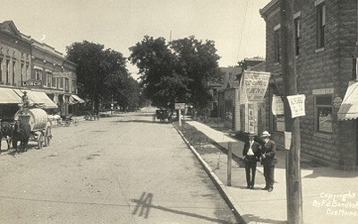 This image shows a panoramic view of an intersection in the business district of Iowa City. A few pedestrians are standing on the sidewalks, and several horse-drawn buggies are tied at hitching posts. The street is lined with 2-3 story brick buildings. Electrical poles are present on both sides of the center street and on one side of the street to the left. Each pole carries several electrical wires.