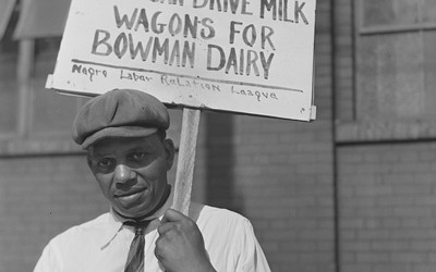 An African American man standing in a picket line for the Negro Labor Relation League with a sign protesting Bowman Dairy in Chicago, Illinois.
