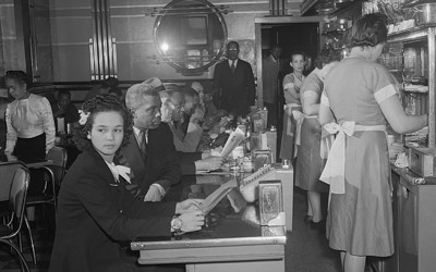 African Americans eating at a local Chicago restaurant owned by African American Mr. E. Norris in 1942.  Most diners and employees are black, and several small businesses in this area of Chicago were owned and operated by African Americans who had migrated north during the Great Migration.