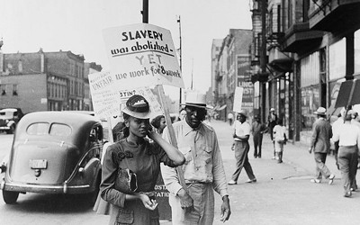 African Americans standing in a picket line outside a midtown business in Chicago, Illinois, in 1941 protesting the wage earned by African Americans compared to others.