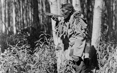 A Northwest Native American man, a member of the Cree tribe, in the woods calling a moose with a blowing horn.