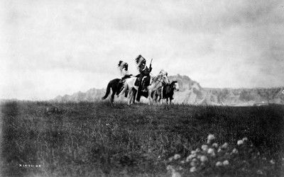 Three Sioux Native Americans on horseback.