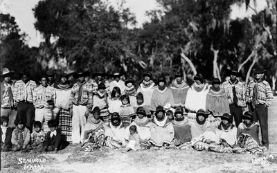 Seminole men, women and children are posing outdoors.