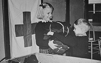 Image shows two young kids at the Red Cross in Des Moines, IA packing clothing for refugees during World War Two.