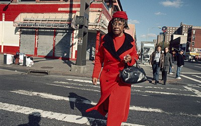 Photograph shows a woman in a bright red coat with matching hat, walking in a crosswalk.