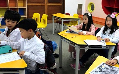 Korean students using books to complete an assignment.