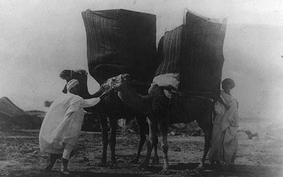Image shows two men in the Sahara with very large wares bags on the backs of two camels.