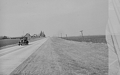 Image of a car driving through Grundy County, Iowa.  The image shows a farm in the background and the road is passing through fertile farmland.