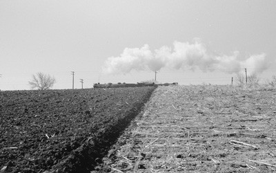 Image of Iowa land that has been freshly plowed on one side of the image, and not plowed on the other.  There is a train and telephone poles in the background.