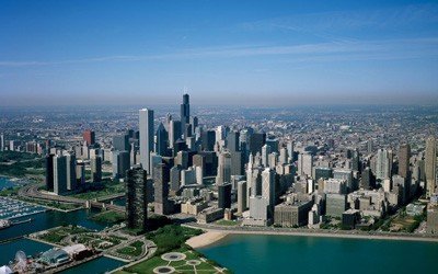 Dozens of skyscrapers seen near the shore of Lake Michigan in this photograph of downtown Chicago.  Navy pier visible in the foreground.  Photo is too high up to see any vehicles or pedestrians.