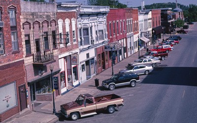 Landscape photograph of main street with multiple buildings visible along with sidewalks, lampposts, trucks, and cars.