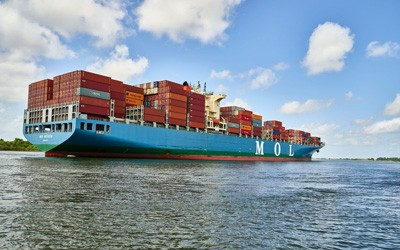 "Color photo of a loaded cargo ship navigates the Savannah River.  ""MOL"" is visible on the side of the ship."