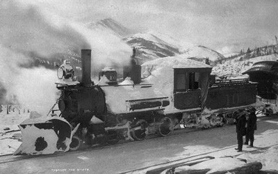 Snow-covered locomotive stopped on railroad tracks with mountains visible in the background.  Two men stand near the train in the foreground.