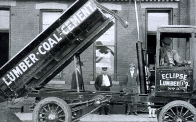 "Old-fashioned delivery truck with box hoisted in the air.  ""Lumber - Coal - Cement"" printed on the side of the box, and four men are also seen in the photo."