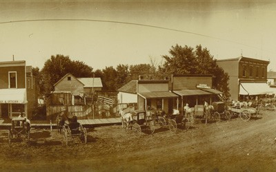 Landscape photo of Main Street in Elliott, Iowa with many buildings, awnings, and horse-drawn wagons parked in front of buildings.