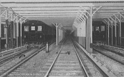 Three subway tracks visible along with many structural support poles.  One inbound and one outbound subway train are visible.