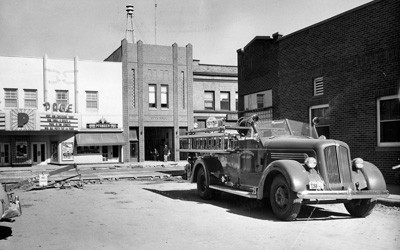 1950s motorized fire truck seen parked in a parking lot with a street construction happening in the background.