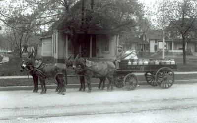 Horse-drawn wagon filled with milk cans in a residential section of Des Moines.