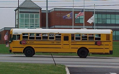 Large, modern school bus driving on street pictured with school building in background.