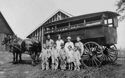 "Large, horse-drawn wagon with four older and six younger students posed in front of it.  ""Webster Consolidated School District"" is painted on the side of the wagon."