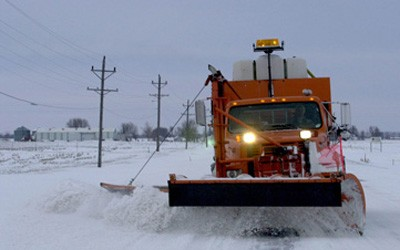 Large, orange snowplow removing snow on a paved road somewhere in rural Iowa.  The only person in the photo is the driver of the snowplow.