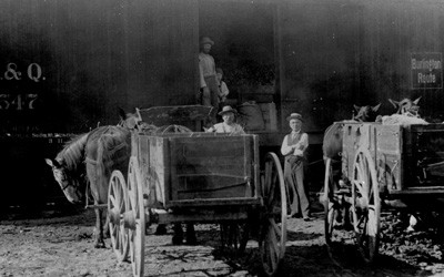 Two horse-drawn wagons parked near train cars.  Doors are open on train cars, and three men and a child are also seen in the photo.