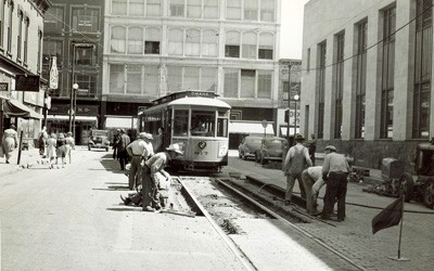 Parked streetcar seems to wait for workers to finish repairs to rails and roadway in front of it.  Four story buildings seen in the background, and two story buildings on either side of the streetcar along with parked cars and a few pedestrians.