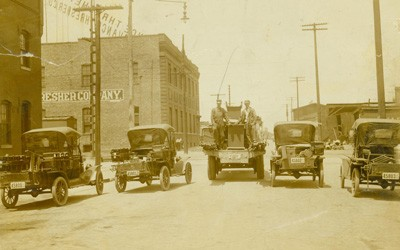 "Four ""Model T"" roadsters and one Peerless Truck parked on a Des Moines street.  Electrical poles and brick buildings are also visible."