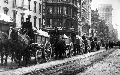 Six, horse-drawn, snow-piled wagons lined up outside of brick buildings and next to streetcar tracks in New York City.