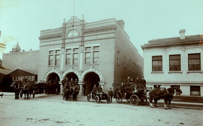 Fire Station Number One is an ornate brick building with three horse-drawn fire wagons and one early automobile firetruck all displayed in the front of the building along with firefighters.