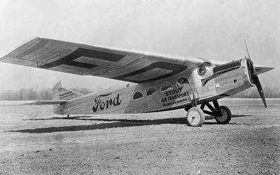 "Small, propeller airplane with ""Ford"" painted on the side."